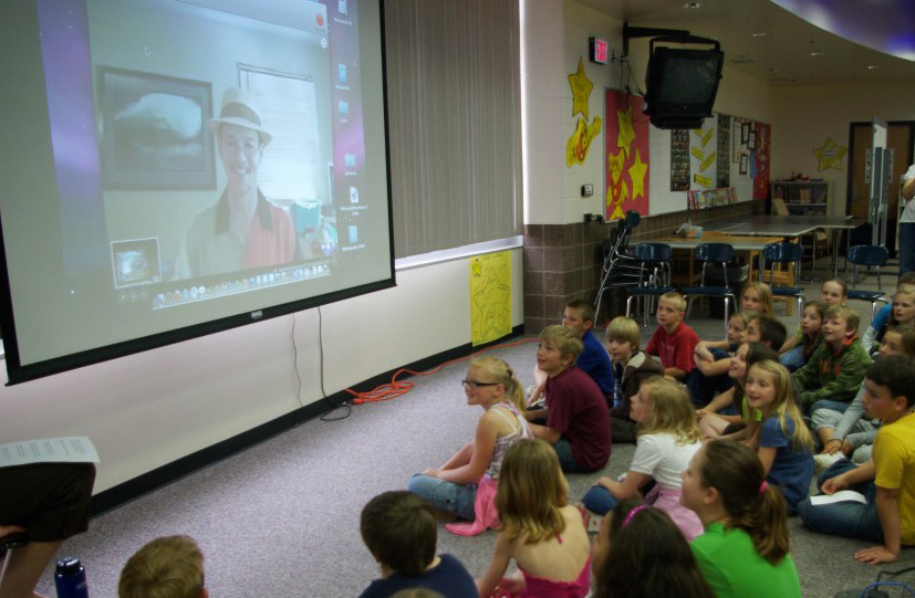 A classroom of kids watching Bruce on the video screen.